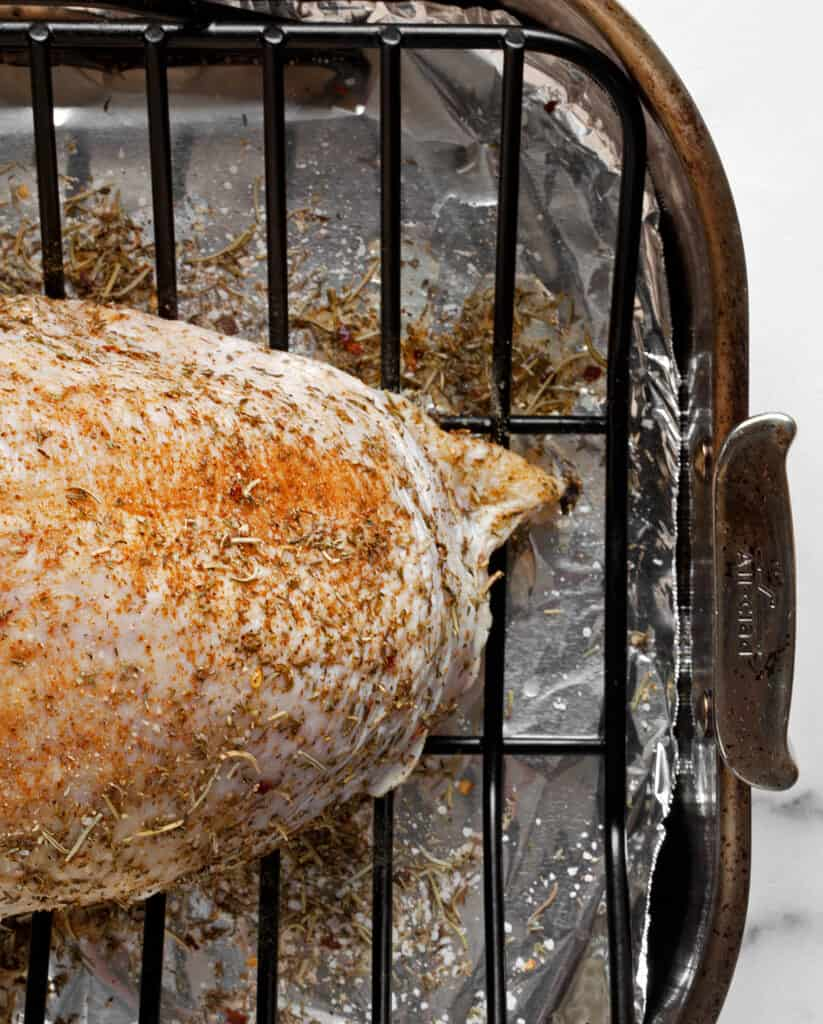 Bone-in turkey breast rubbed with dry seasoning mix on a rack in a roasting pan