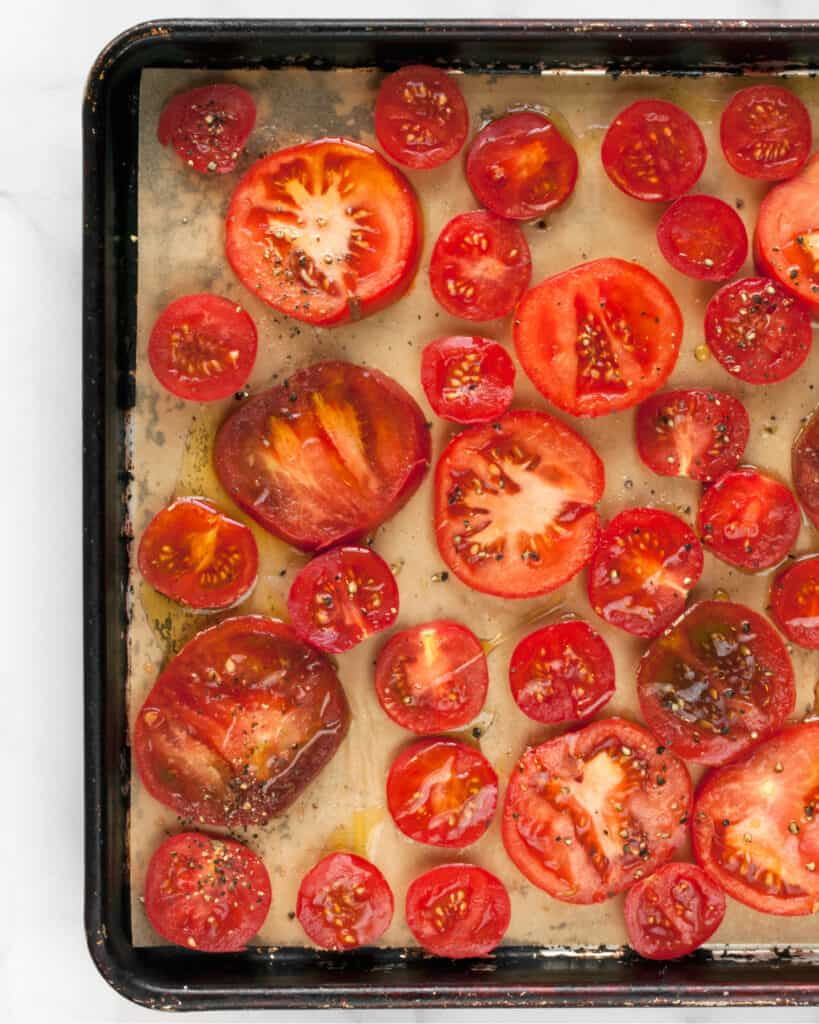 Raw sliced tomatoes on sheet pan drizzled with olive oil