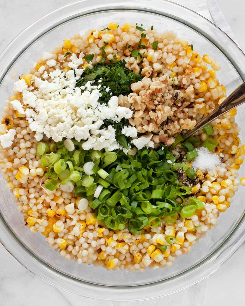 Stirring together the corn, couscous, scallions and other ingredients