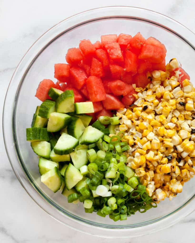 Salad ingredients include watermelon, cucumbers, grilled corn & scallions
