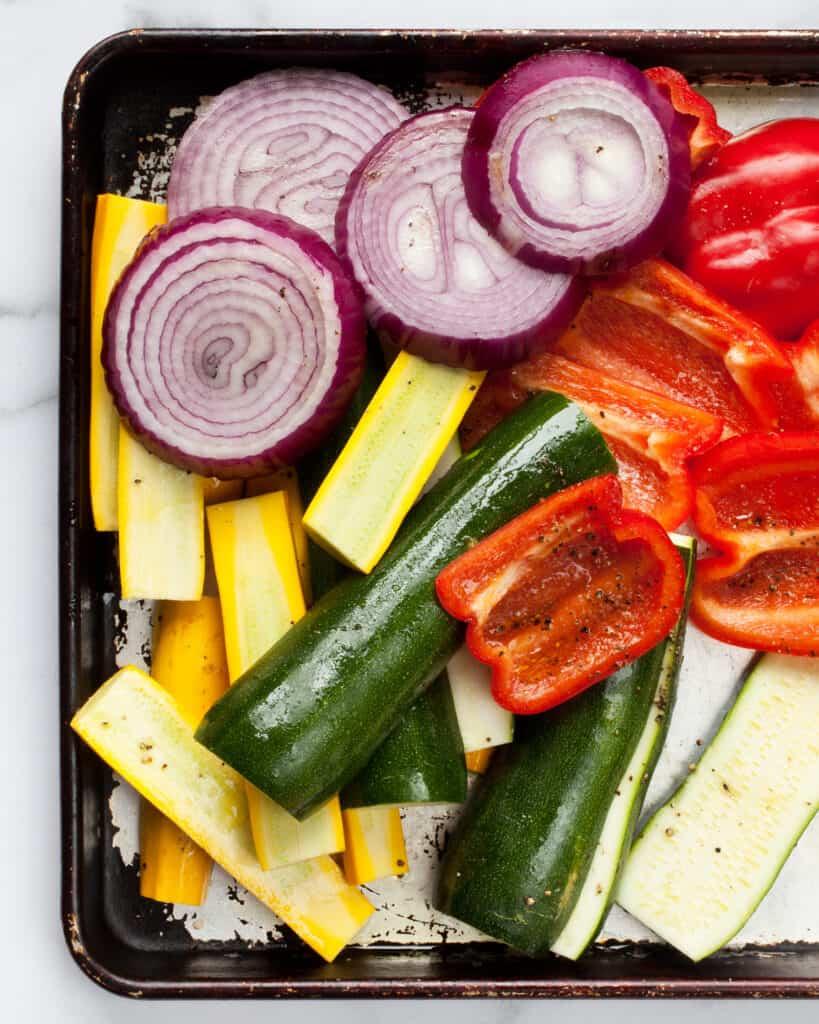 Sliced vegetables on sheet pan