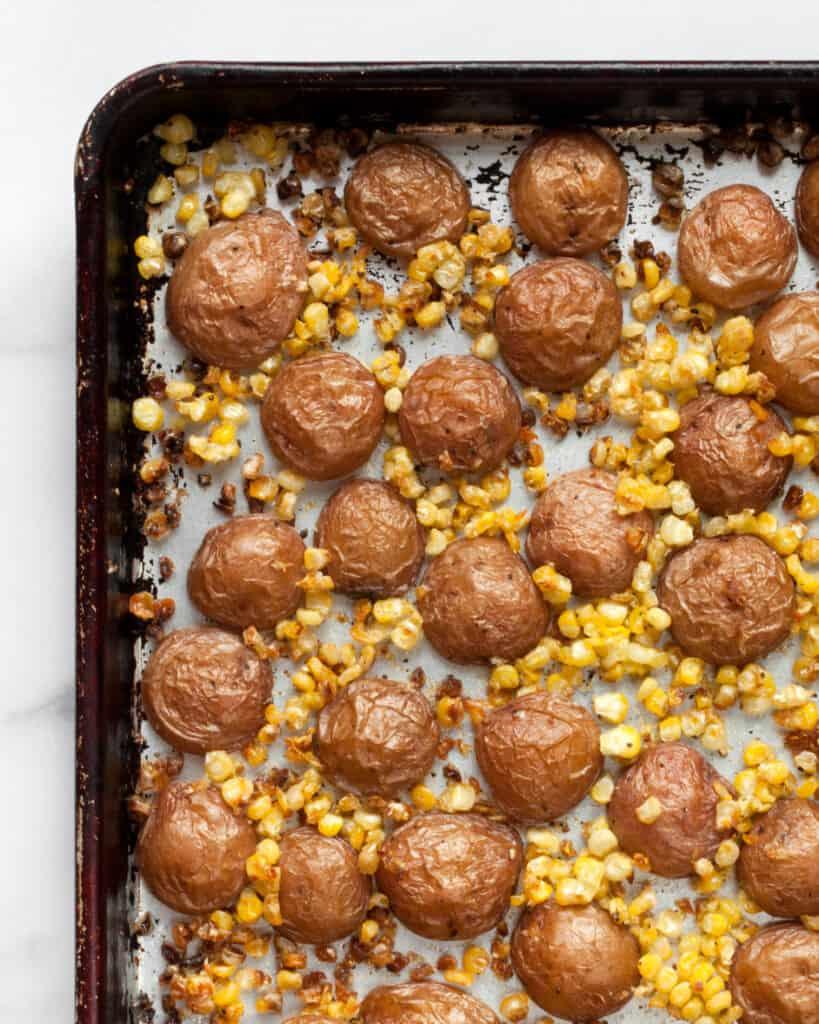 Potatoes and corn on sheet pan