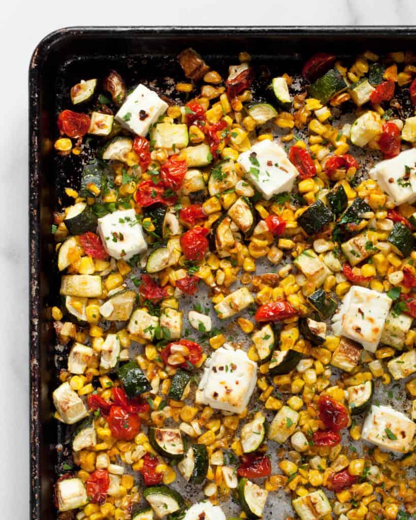 Baked feta, zucchini, corn & tomatoes on a sheet pan