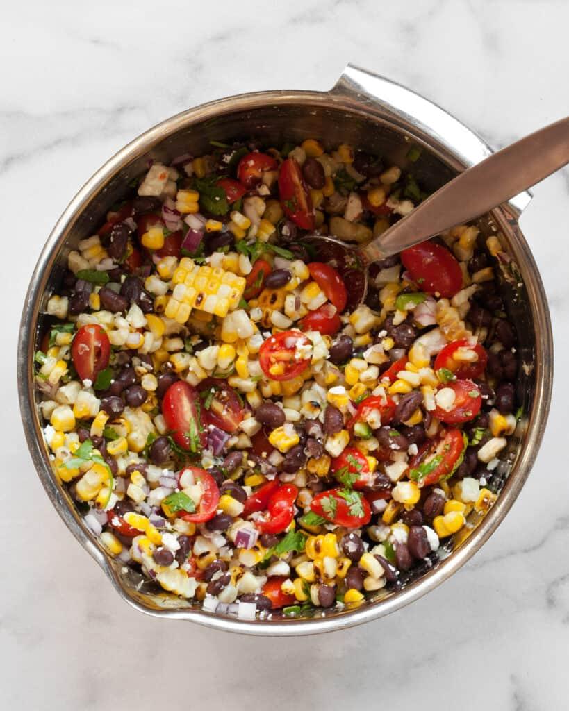 Stirring together salad corn black bean salad ingredients