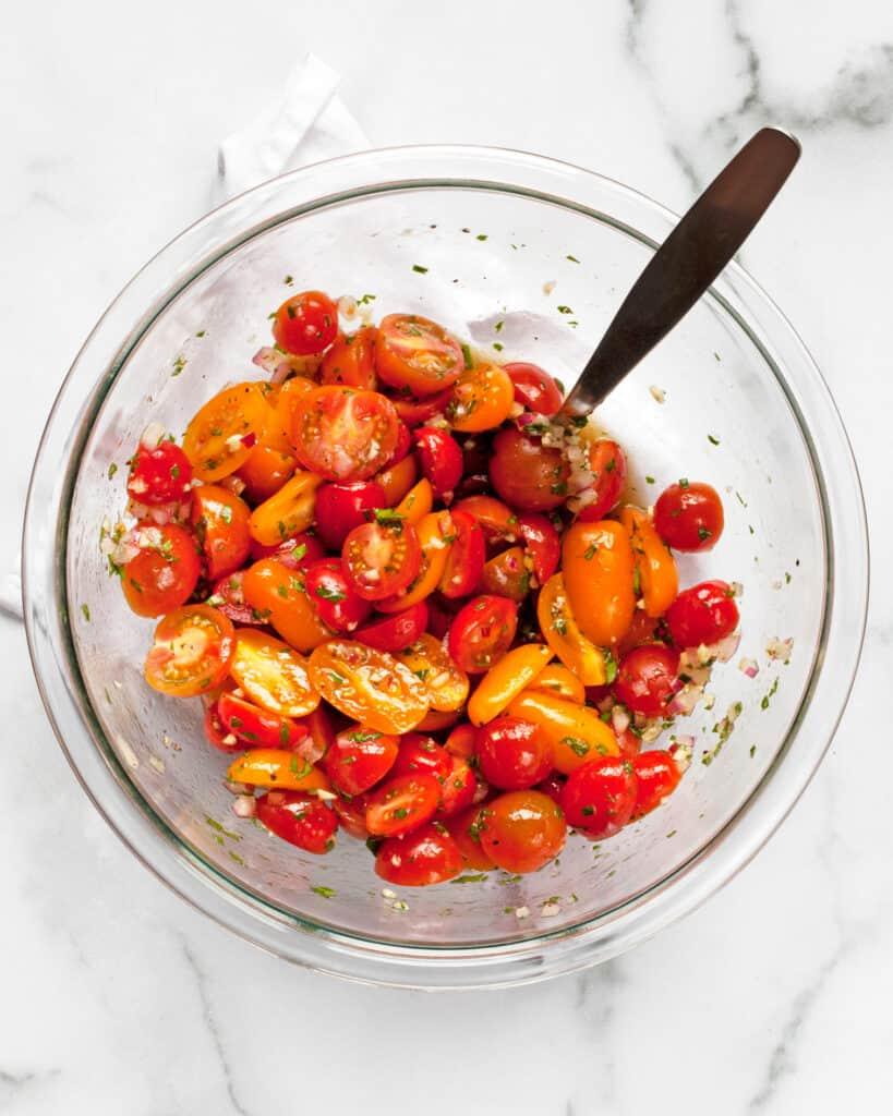 Stirring cherry tomatoes in marinade