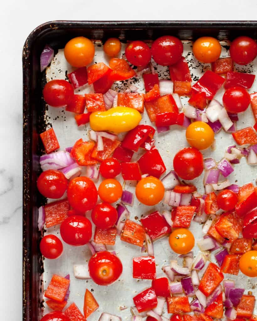 Cherry tomatoes, peppers and onions on a sheet pan