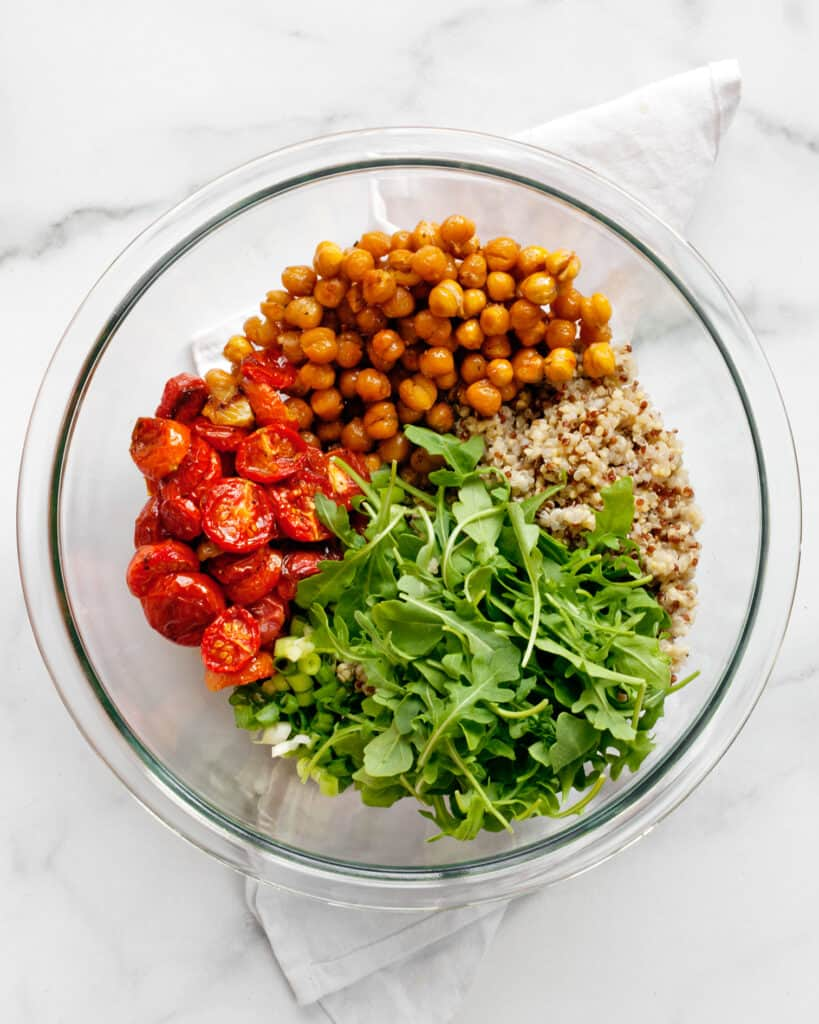 Roasted chickpeas and tomatoes in a bowl with arugula, quinoa and scallions