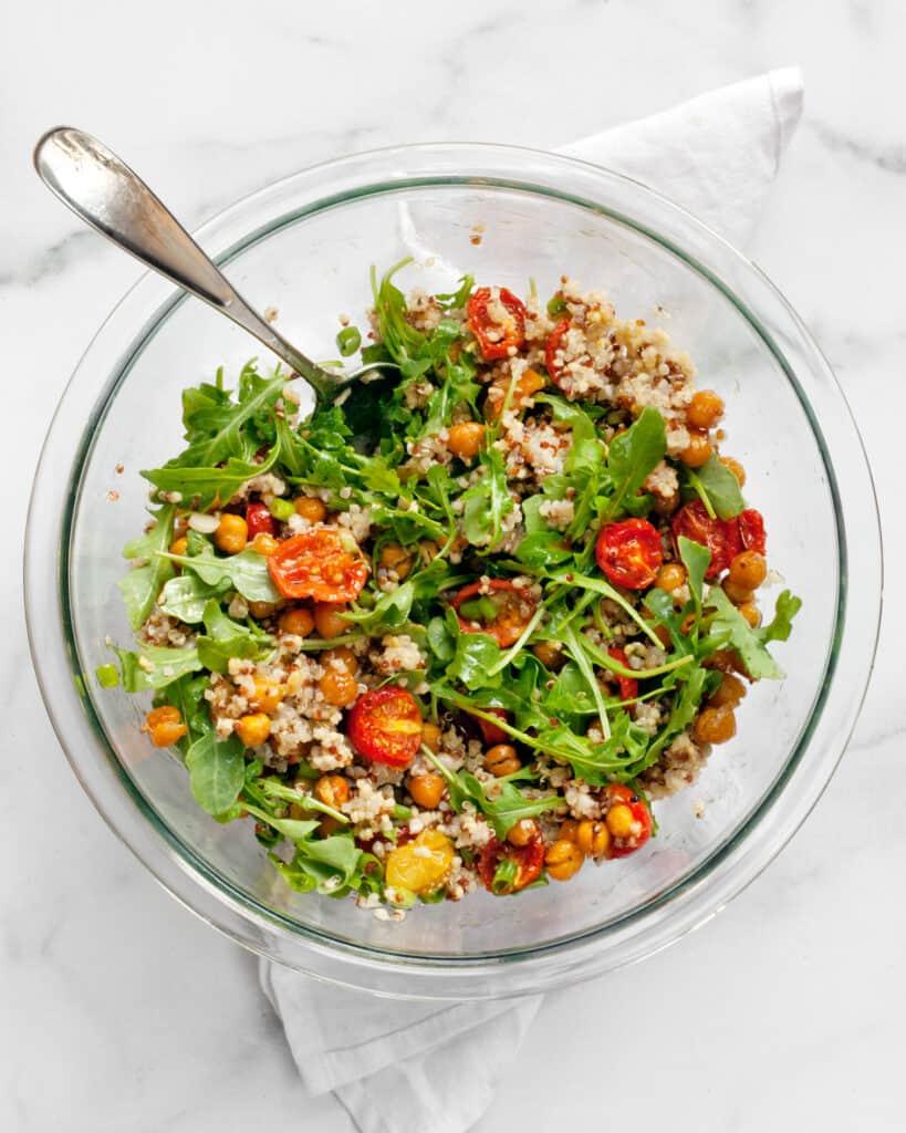 Stirring together roasted tomato chickpea quinoa salad