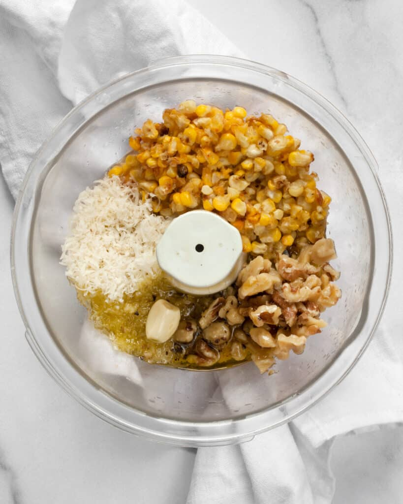 Roasted corn, parmesan, walnuts, garlic, olive oil and lemon juice in a bowl for pesto