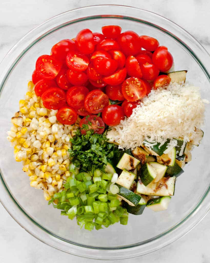 Tomatoes, corn, zucchini, scallions and parmesan in a bowl