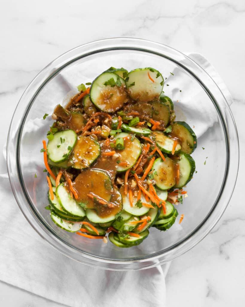 Stirring vinaigrette into cucumber salad