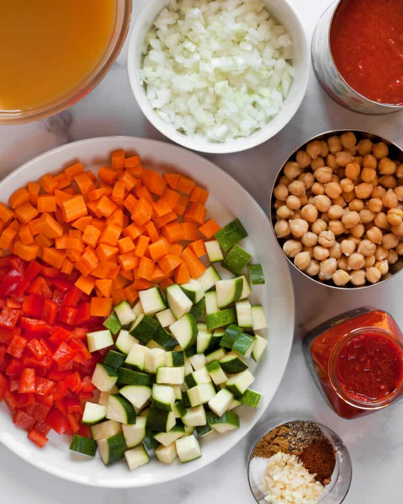 Carrots, red peppers, zucchini, harissa and other soup ingredients