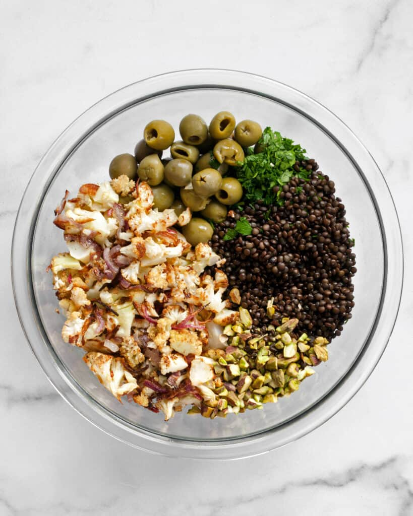 Combining cauliflower, onions, lentils, olives, pistachios and parsley in a bowl